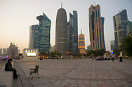 View from the corniche of people and buildings at sunset in the modern downtown of Doha, Qatar. On the right, Muslims pray beside a mobile prayer unit.