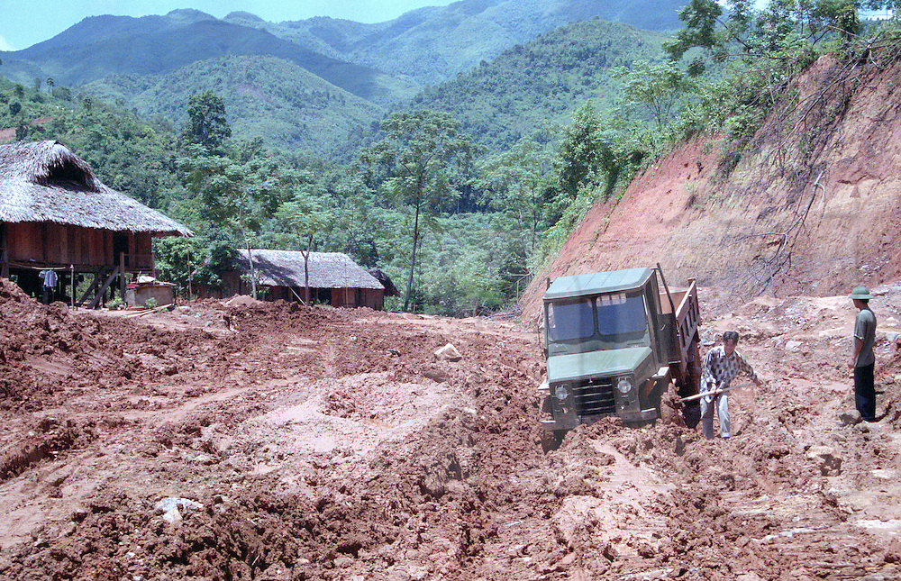 A truck driver digs out his truck from wet clay during rainy season. Vietnam, Southeast Asia
