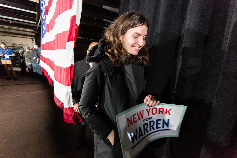 """Long Island City, NY – 8 March 2019. Massachusetts Senator and Democratic Presidential candidate Elizabeth Warren drew an enthusiastic crowd at an organizing rally for her 2020 presidential campaign in Long Island City. A woman enters the venue prior to the event carrying a sign that reads """"New York Cor Warren."""""""