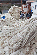 A Nepalese male factory worker sits and sorts through the newly arrived bundles of raw wool in the store area of the R.C Rug Factory in the Narayanthan area of Kathmandu, Nepal. The company export rugs and carpets to Europe the U.S and Canada, and rely on the GoodWeave certificate of approval to boast excellent quality and fair conditions for its workers, as the carpet factory industry in Nepal is notorious for providing poor working conditions and forcing young children into labour.