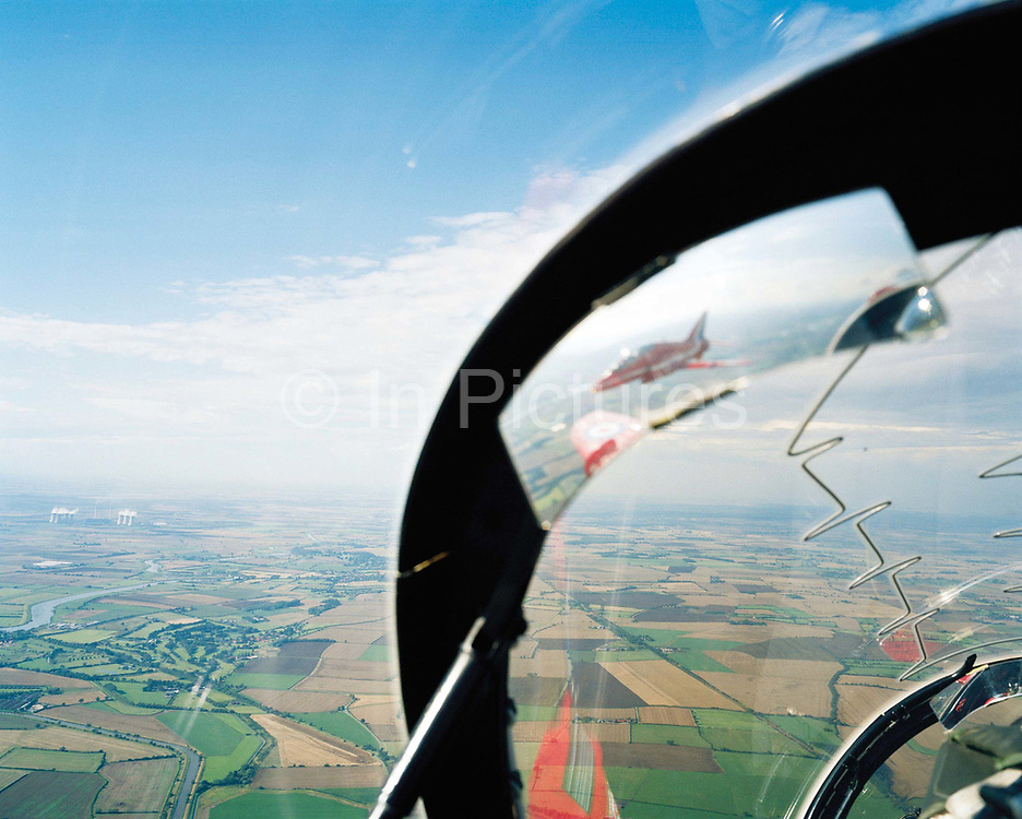 From the rear seat of a 'Red Arrows' Hawk of Britain's Royal Air Force aerobatic team during an In-Season Practice (ISP) training flight near their base at RAF Scampton. Through the explosive Plexiglass canopy, we look towards the Lincolnshire countryside from an altitude of a few thousand feet. This is the view from the leader's jet during an In-Season Practice (ISP) training flight. Waiting for the other eight members of the team to re-form as an airborne squadron, they fly in front of a local crowd at the airfield. The team work their way through a 25-minute series of display manoeuvres that are loved by thousands at summer air shows. After some time off, spare days like this are used to hone their aerobatic and piloting skills before re-joining the air show circuit. Since 1965 they've flown over 4,000 shows in 52 countries.