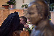 Moscow, Russia, 02/04/2005..As Pope John Paul ll lies close to death in the Vatican, Russian Catholics pray for him inside the Cathedral of the Virgin Mary's Immaculate Conception, Russia's largest Roman Catholic church. A worshipper prays beside a bust of Pope John Paul ll.