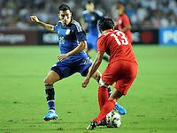 Nicolas Gaitan of Argentina, left, challenges Cheung Kin-fung of Hong Kong during a friendly football match in Hong Kong, China, 14 October 2014.<br /> <br /> Lionel Messi needed just six minutes to make his mark in Argentina's 7-0 rout of Hong Kong in a friendly at Hong Kong Stadium on Tuesday (14 October 2014). The Barcelona star Messi scored twice after going on as a substitute for the last 30 minutes of the game to celebrate the 100th anniversary of the Hong Kong Football Association. Napoli striker Gonzalo Higuain and Benfica's Nicolas Gaitan also scored two goals each after Sevilla's Ever Banega had opened scoring in the 19th minute.