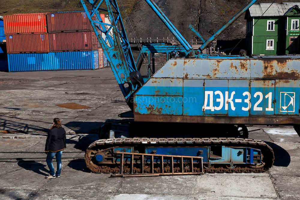 Woman standing by crane, Barentsburg harbour, a Russian coal mining town in the Norwegian Archipelego of Svalbard. Once home to about 2000 miners and their families, less than 500 people now live here.