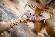 Priest climbing rope to the 6th-century monastery, Debre Damo. West of Adigrat, Tigray Region. Ethiopia, Horn of Africa