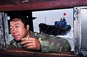 Fisherman at the helm of his fishing trawler off the island of Jin Shan, China
