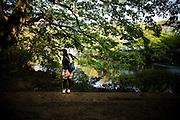 TOKYO, JAPAN, 28 APRIL - Kichijoji -A young woman in front of trees and pond turn her face to someone outside of the frame.  - APRIL 2012 [FR] à Kichijoji, une jeune femme face à des arbres et un étang se retourne avec un regard complice vers l'exterieur