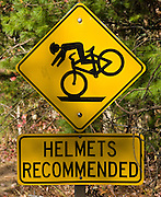 """""""Helmets Recommended"""" for bicyclists sign in Cades Cove, an isolated valley located in the East Tennessee section of Great Smoky Mountains National Park, USA. Cades Cove was once home to numerous settlers. Today Cades Cove is the most popular destination for visitors to the park, attracting over two million visitors a year, due to its well preserved homesteads, scenic mountain views, and abundant display of wildlife. Cades Cove is a type of valley known as a """"limestone window,"""" created by erosion that removed the older Precambrian sandstone, exposing the younger Paleozoic limestone beneath. The weathering of the limestone produced deep, fertile soil, making Cades Cove attractive to early farmers. More weather-resistant formations, such as the Cades sandstone which comprises Rich Mountain to the north and the Elkmont and Thunderhead sandstones which comprise the Smokies crest to the south have surrounded the cove, leaving it relatively isolated within the Great Smokies."""