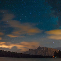 The Milky Way soars over Mount Rundle and Two Jack Lake in Banff National Park, Alberta, Canada.  The clouds are lit by lights from Calgary, Banff and the Trans-Canada Highway.