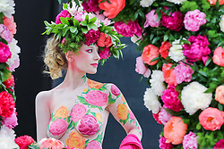 © Licensed to London News Pictures. 20/05/2019. London, UK. A model wearing a floral display hat and body art poses for photographers at the Primrose Hill stand. <br /> *** Warning - Nudity***.<br /> The Royal Horticultural Society Chelsea Flower Show is an annual garden show held over five days in the grounds of the Royal Hospital Chelsea in West London. The show is open to the public from 21 May until 25 May 2019. Photo credit: Dinendra Haria/LNP