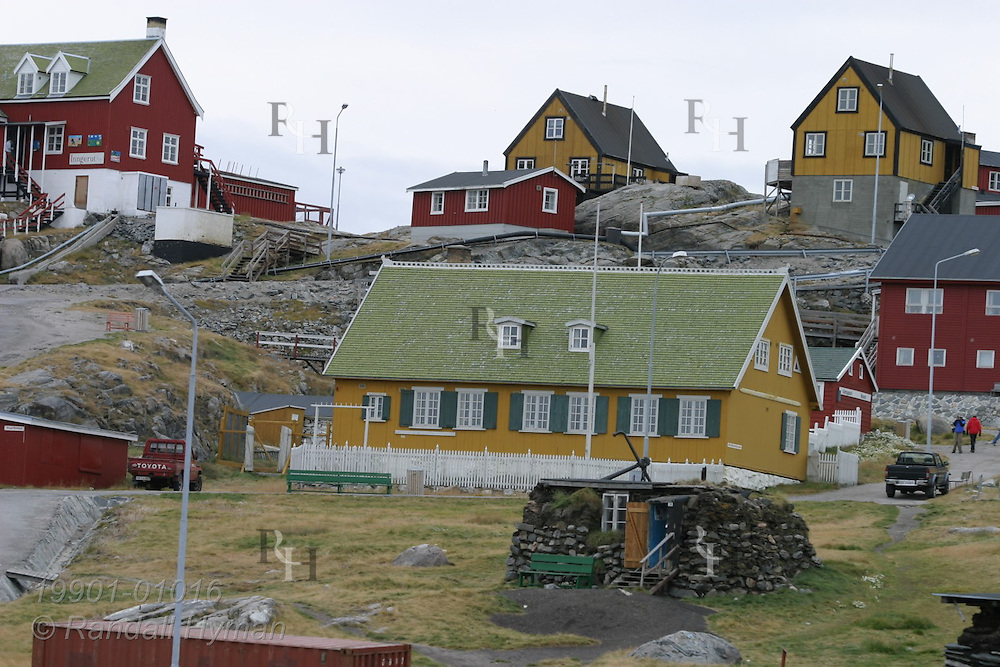Colorful red, white and yellow buildings sit on rocky hill in the island town of Uummannaq, Greenland.