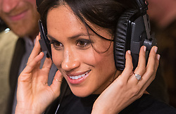 Meghan Markle listens to a broadcast through headphones during a visit to youth-orientated radio station, Reprezent FM, in Brixton, south London to learn about its work supporting young people.