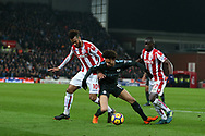 Leroy Sane of Manchester City © tries to go past Maxim Choupo-Moting (l) and Badou Ndiaye of Stoke City. Premier league match, Stoke City v Manchester City at the Bet365 Stadium in Stoke on Trent, Staffs on Monday 12th March 2018.<br /> pic by Andrew Orchard, Andrew Orchard sports photography.