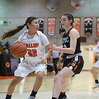 Gallup Bengal Kennedy Smiley (22) drives to the basket as Aztec Tiger Daniella Sanders (2) defends Tuesday night at Gallup High School in Gallup. Gallup beat the Tigers 51-11.