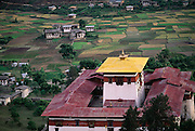 Paro Valley, Bhutan with the Paro Dzong in the foreground and rammed earth houses and rice fields behind. From Peter Menzel's Material World Project.