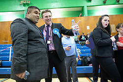 © Licensed to London News Pictures . 12/12/2019. Bury, UK. Conservative Party supporters (centre and left) and Labour Party supporters (r) watch results being declared on TV screens at the count for seats in the constituencies of Bury North and Bury South in the 2019 UK General Election , at Castle Leisure Centre in Bury . Photo credit: Joel Goodman/LNP
