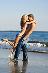 Playful couple at the beach laughing and sharing a moment together