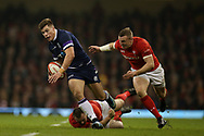Huw Jones of Scotland © breaks past a tackle from Ken Owens and Hadleigh Parkes of Wales (r)  in the 1st half. Wales v Scotland, NatWest 6 nations 2018 championship match at the Principality Stadium in Cardiff , South Wales on Saturday 3rd February 2018.<br /> pic by Andrew Orchard, Andrew Orchard sports photography