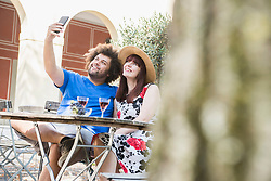 Young couple taking selfie using mobile phone camera at outdoor restaurant