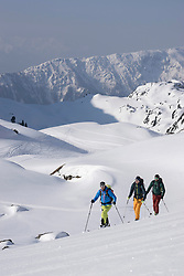 Ski mountaineers climbing on snowy peak, Tyrol, Austria