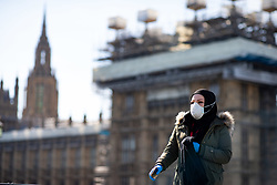 © Licensed to London News Pictures. 23/03/2020. LONDON, UK. A woman walks along a quiet Westminster Bridge this afternoon. The government has advised people to practice social distancing measures that help reduce the transmission of Coronavirus (COVID-19). Photo credit: Luke Dray/LNP