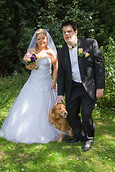 Visually impaired bride and groom posing for photos with guide dog.