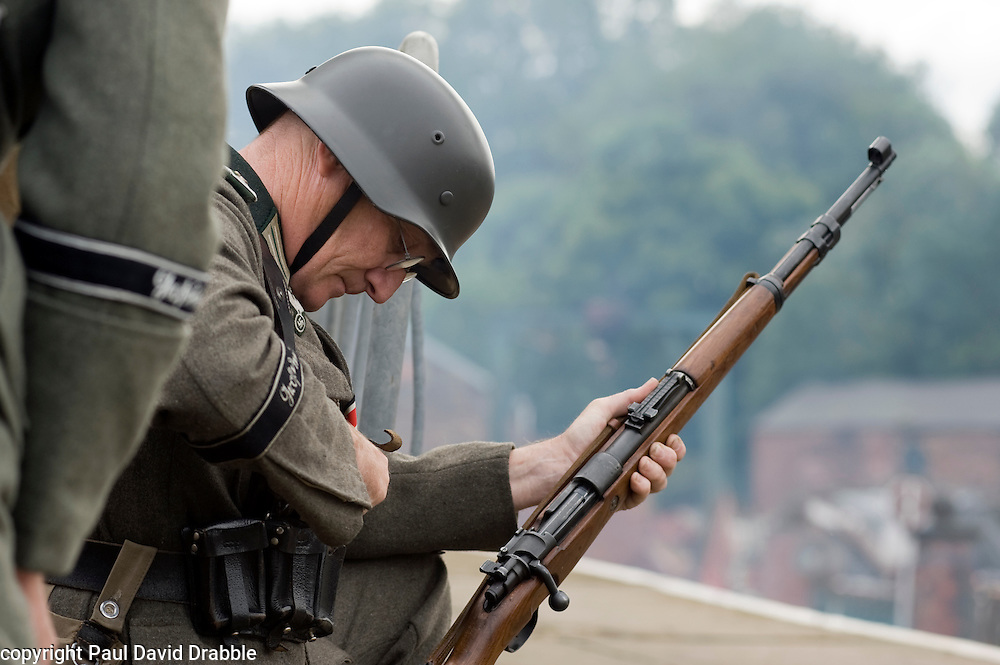Re-enactor dressed as a Panzer Grenadier from the Elite German Heer GrossDeutschland Division loads a blank fire K98 Rifle  during a battle re-enactment at the Elsecar Heritage Centre 1940s Wartime Weekend 4 September 2010 .Images © Paul David Drabble..