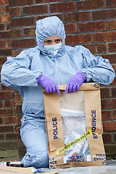 © Licensed to London News Pictures. 31/03/2019. London, UK. A forensic Officer seals the bag which contains the victim's belongings on Fore Street in Edmonton, north London where a person was stabbed just after 9.30am this morning. The victim was taken to a hospital by Air Ambulance and his condition is unknown. Photo credit: Dinendra Haria/LNP