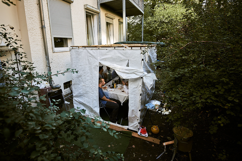 Germany, Berlin, 2018/09/27<br /> <br /> Rabbi Shlomo Afanasev and some friends celebrate Sukkot in his sukkah in a backyard behind his house in Berlin. The orthodox family is part of Kahal Adass Jisroel, an orthodox community situated in Berlin's neighborhood Prenzlauer Berg and supported by the Ronald S. Lauder Foundation.<br /> <br /> Jewish life in Germany occurs in a myriad of ways – being Jewish is just as much a question of identity as it is one of religion. The Jewish community in Germany is however fairly small, official numbers state that only about 96.000 Jews live in the country. Often only perceived through debates of anti-semitism and holocaust commemorations and displayed in the media in a stereotypical way, I aim to explore everyday life of contemporary Judaism in Germany in all its facets and diversity. (Photo by Gregor Zielke)