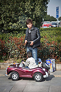 A man smoking a cigarette while his child plays in a toy car in Yiwu, Zhejiang Province, China on 06 March  2013. The city of Yiwu is known as one of China's largest trading centers for small merchandise and light industry, drawing buyers from around the world. Uncertain global demand, a stronger yuan currency and rising labour costs have taken their toll on Chinese exporters, but analysts believe sales could pick up modestly in 2014 due to improved demand from the United States and Europe.