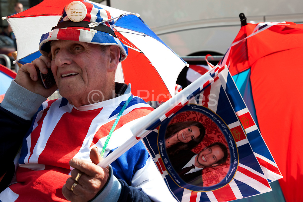Delighted to have a prime spot, Terry Hutt camps out to see the Royal couple. Preparations for the Royal Wedding as the first of the public start camping out on the parade route. Here opposite Westminster Abbey these patriotic royalists take their prime spot some three days before the wedding day itself.