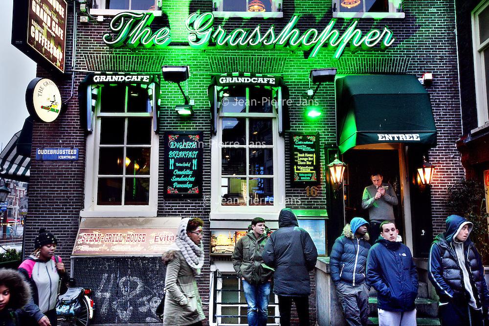 Nederland, Amsterdam , 19 januari 2014.<br /> Eén van de beroemdste coffeeshops van Amsterdam, The Grasshopper in de Oudebrugsteeg, mag geen softdrugs meer verkopen. Vanaf begin dit jaar ontbreekt daar de gedoogverklaring voor.<br /> Een poging van de eigenaren om via een kort geding verlenging van een dergelijke verklaring af te dwingen, is mislukt. Gisteren oordeelde de Amsterdamse rechtbank dat de gemeente Amsterdam zorgvuldig heeft gehandeld en dus geen nieuwe toestemming hoeft te verlenen.Dat betekent dat de Grasshopper oude stijl gaat verdwijnen. Het zal nogal wat teweegbrengen onder vooral de grote groep backpackers die niet zelden, vers uit het Centraal Station, de Grasshopper als eerste Amsterdamse bezienswaardigheid aandeden.Rode LoperDeze centrale plek blijkt de achilleshiel van de Grasshopper. Het ligt aan de Rode Loper - het gebied dat de gemeente mooi, veilig en beter bereikbaar wil maken. Tegelijkertijd valt de Oudebrugsteeg onder het Coalitieproject 1012, waarin de gemeente de Wallen aantrekkelijker, gevarieerder en veiliger wil maken.De Grasshopper heeft in juli 2009 al een brief gekregen waarin de gemeente stelt dat de gedoogverklaring nog één keer zal worden verlengd, tot 1 december 2012. Later werd dat opgerekt tot 4 januari 2014.<br /> Foto:Jean-Pierre Jans
