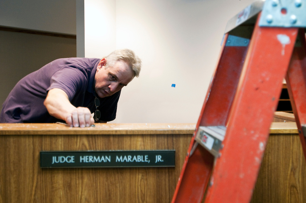 Matt Dixon | The Flint Journal..Craig Keelor of Electronic Restoration Services inspects a microphone port before running new cables in a courtroom in the McCree Courts & Human Services Building, Thursday, Feb. 17.