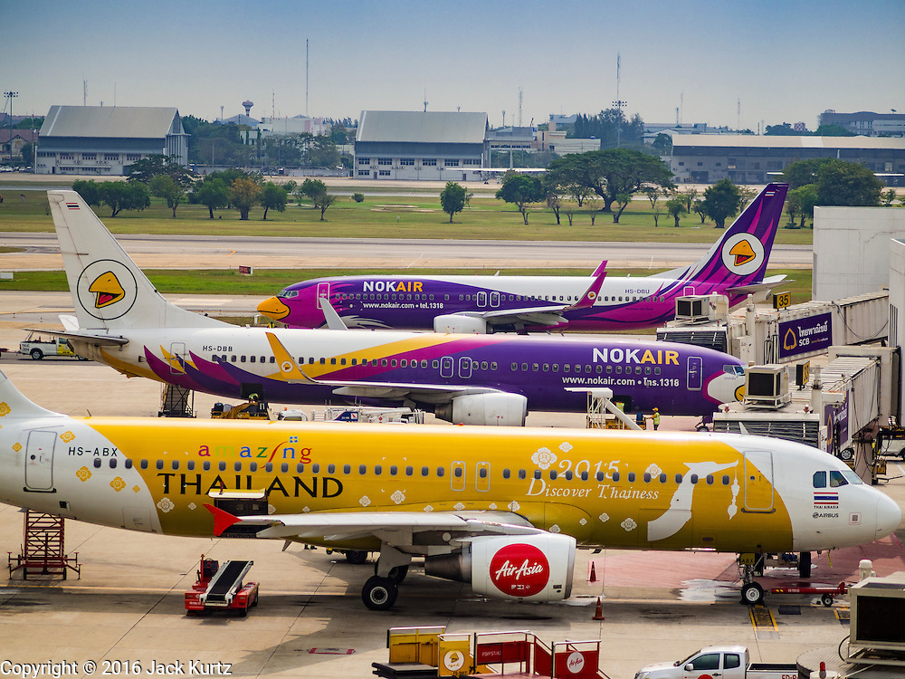"""23 FEBRUARY 2016 - BANGKOK, THAILAND:  An Air Asia Airbus in front of Nok Air aircraft on an apron at Don Mueang Airport. Nok Air, partly owned by Thai Airways International and one of the largest and most successful budget airlines in Thailand, cancelled 20 flights Tuesday because of a shortage of pilots and announced that other flights would be cancelled or suspended through the weekend. The cancellations came after a wildcat strike by several pilots Sunday night cancelled flights and stranded more than a thousand travelers. The pilot shortage at Nok comes at a time when the Thai aviation industry is facing more scrutiny for maintenance and training of air and ground crews, record keeping, and the condition of Suvarnabhumi Airport, which although less than 10 years old is already over capacity, and facing maintenance issues related to runways and taxiways, some of which have developed cracks. The United States' Federal Aviation Administration late last year downgraded Thailand to a """"category 2"""" rating, which means its civil aviation authority is deficient in one or more critical areas or that the country lacks laws and regulations needed to oversee airlines in line with international standards. At the same time, the Thai government has expressed an interest in Thai Airways acquiring a stake in Air Asia (Thailand). Executives from the two companies are expected to meet this week to discuss the proposal.        PHOTO BY JACK KURTZ"""