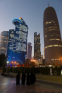 View from the corniche of people and buildings at dusk in the modern downtown of Doha, Qatar