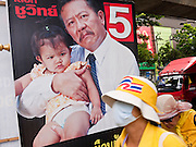"""22 JUNE 2011 - BANGKOK, THAILAND: Thai Yellow Shirts, who are calling for a """"no"""" vote in the election, walk past a campaign poster in Bangkok, Thailand. Yingluck Shinawatra, leader of the Pheua Thai party is running against  incumbent Prime Minister Abhisit Vejjajiva, head of the Democrat party. Yingluck is the youngest sister of exiled former Prime Minister Thaksin Shinawatra, deposed by a military coup in 2006. Yingluck is currently leading in opinion polls, running well ahead of the Democrat party, which in one form or another has ruled Thailand for most of the last 60 years.   Photo by Jack Kurtz"""