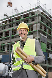 Portrait of a happy male site manager standing with blueprints at a construction site, Bavaria, Germany
