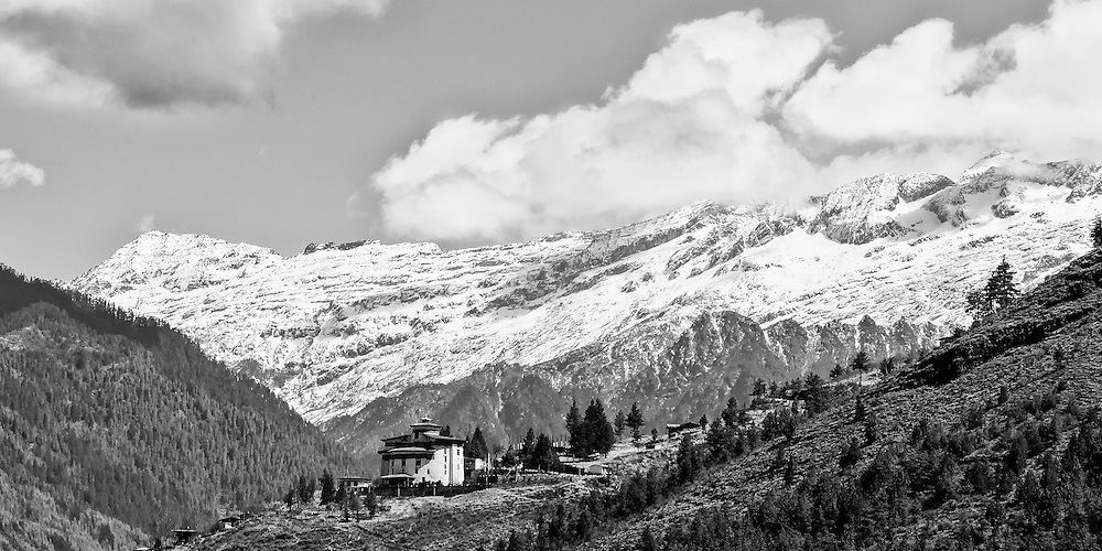 Bhutan, Paro, Ta Dzong a 17th century fortess, now Bhutan's National museum is in the foreground and snow covered Himalayan peaks are in the background D Fine and Sharpening