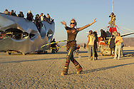 BLACK ROCK CITY, NV – SEPTEMBER 2:  A hula hooper at sunrise on the playa in Black Rock City, Nevada on September 2, 2005.  In the art car behind the hooper there is a wedding taking place. (Photo by Jonathan Kingston/Aurora)