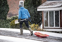 © Licensed to London News Pictures. 08/02/2021. Dunstable, UK. A man carrying a spade pulls a sledge filled with grit, during heavy snowfall in Dunstable, Bedfordshire. Strong easterly winds from Ukraine and the Black Sea are expected to last in to the middle of the week. Photo credit: Ben Cawthra/LNP