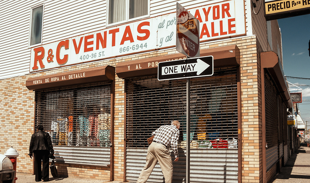 Man and woman looking at closed store window of R&C Ventas 36th St. Union City, NJ 2013