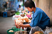 24 JUNE 2011 - CHIANG MAI, THAILAND: A coconut vendor drains coconut juice from the coconuts she's selling in the market in Chiang Mai, Thailand.  PHOTO BY JACK KURTZ
