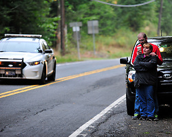 Displaced residents Jason Neff drinks coffee as he comforts his wife Jennifer Neff. Police surround a neighborhood in the Pocono Mountains in search of ambush suspect Eric Matthew Frein who is accused of shooting two Pennsylvania State Troopers Saturday Sept. 20th, 2014 in Canadensis, Pennsylvania (AP Photo/Chris Post)