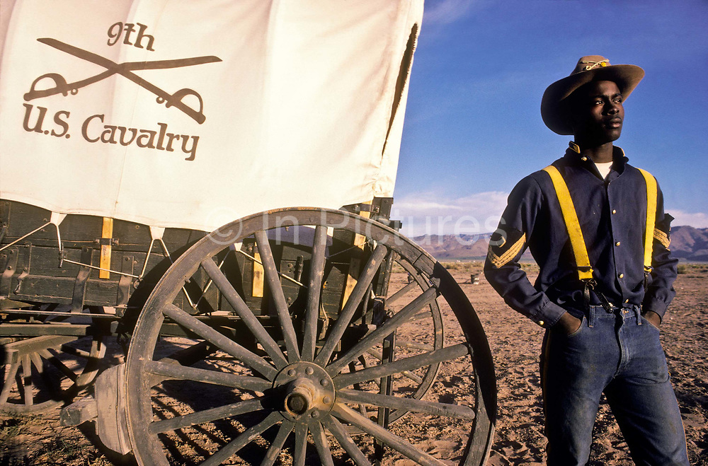 """A group of young juvenile (criminal)  offenders participate in an """"open prison"""" rehabilitation programme designed to build self esteem, courage, purposeful lives, seen here  a young offender in a Nevada landscape. They are known as """"Buffalo soldiers"""" and use the same clothing as Gral Custer and his cavalry used in the American civil war. Most of  the offenders are black, USA. This programme runs by the name of Vision Quest's Wagon Train."""