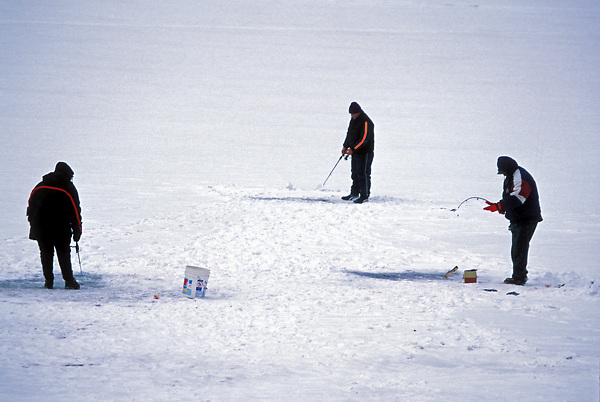 Stock photo of three men ice fishing on a frozen lake