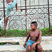Boys playing football at the street, by an abandoned building refered by them as a convent