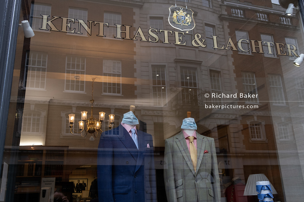 Face coverings are wrapped around the 'necks' of two tailoring dummies in the window of Kent, Haste & Lachter on Sackville Street, during the Coronavirus pandemic, on 24th September, in London, England. As one of the last independent Bespoke Tailors, Kent & Haste are Royal Warrant Holders to HRH The Duke of Edinburgh.