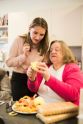 Senior woman with girl cutting apple at rest home