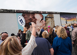 Large tour group taking photos of mural The Kiss painted on original section of Berlin Wall at East Side gallery in Berlin, Germany ...Editorial Use Only