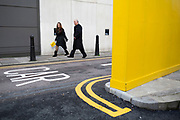 Convergence of yellow in a single frame. A woman carrying a Selfridges shopping bag passes a yellow wall along a road with double yellow lines. London, UK.